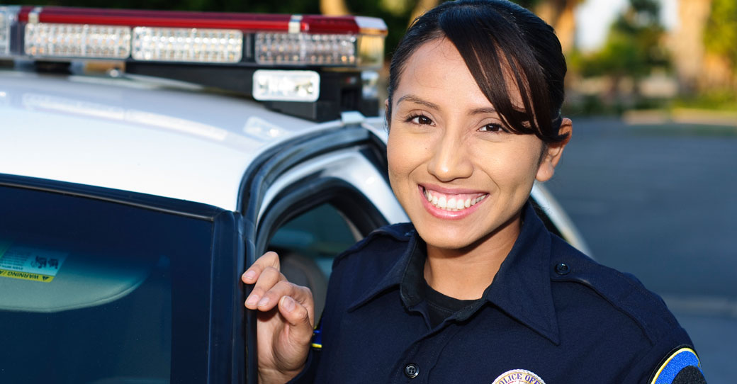 smiling police officer standing next to car